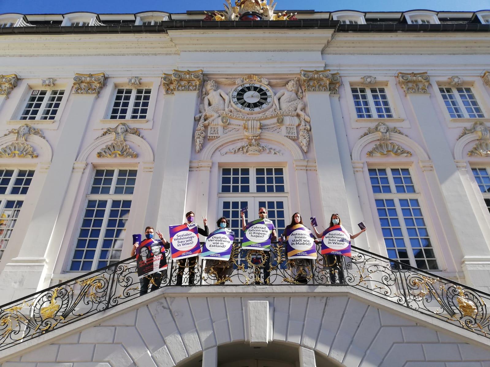 """Sechs Volter*innen stehen auf der Treppe zum Rathaus in Bonn. Sie tragen Umhängeschilder von Volt mit Aufschriften wie """"Sozialer Wohnungsbau wie in Wien?"""", """"Digitalisierung wie in Estland?"""", """"Autoarme Innenstadt wie in Madrid?"""" und """"Fahrrad fahren wie in Kopenhagen?"""""""