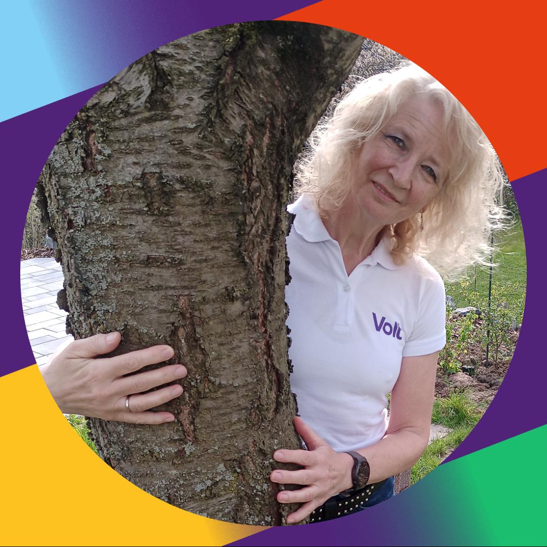 Das Foto habe ich am Tag des Baumes gemacht. Es zeigt eine blonde Frau, die einen Baum umarmt.