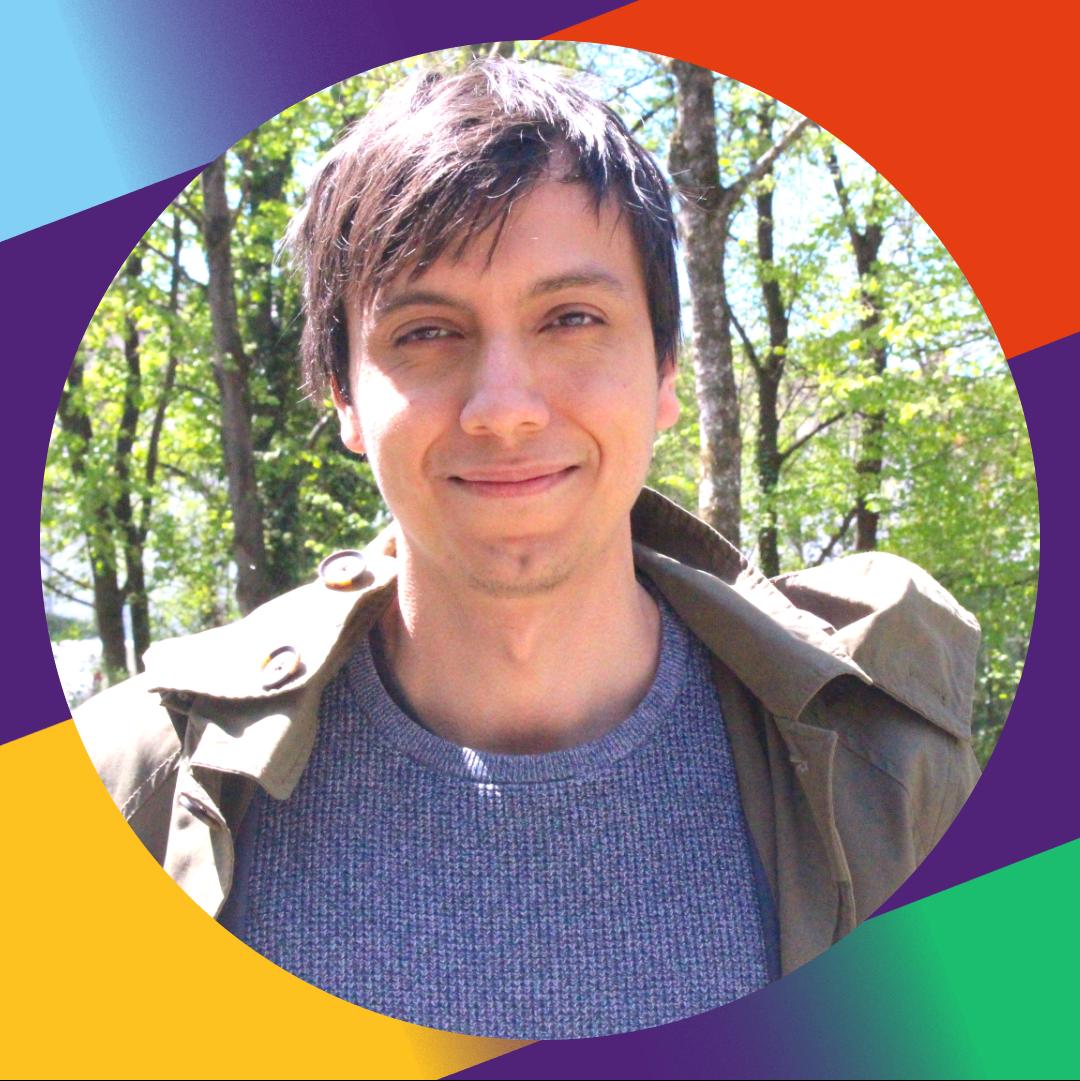 Daniel Burandt lächelt freundlich und befindet sich in einem kleinen Park. Seine Haare bedecken leicht sein Gesicht. Im Hintergrund sind viele Bäume und ein Stück einer Wand mit Graffiti zu sehen.