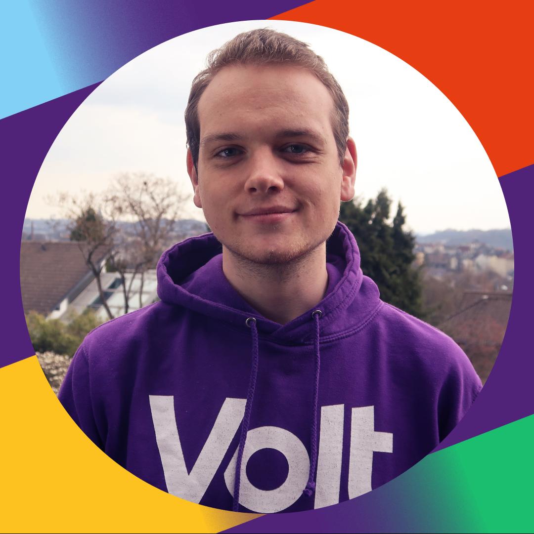 Lars Herbold steht in einem lila Pullover mit weißem Volt Logo lächelnd in der Mitte des Bildes. Im Hintergrund ist unscharf ein Blick über Wuppertal.