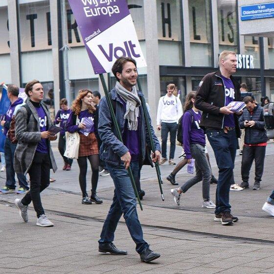 Mehrere Volter*innen laufen durch eine Einkaufspassage in den Niederlanden. Sie tragen Klamotten und Schilder mit Volt-Logo.