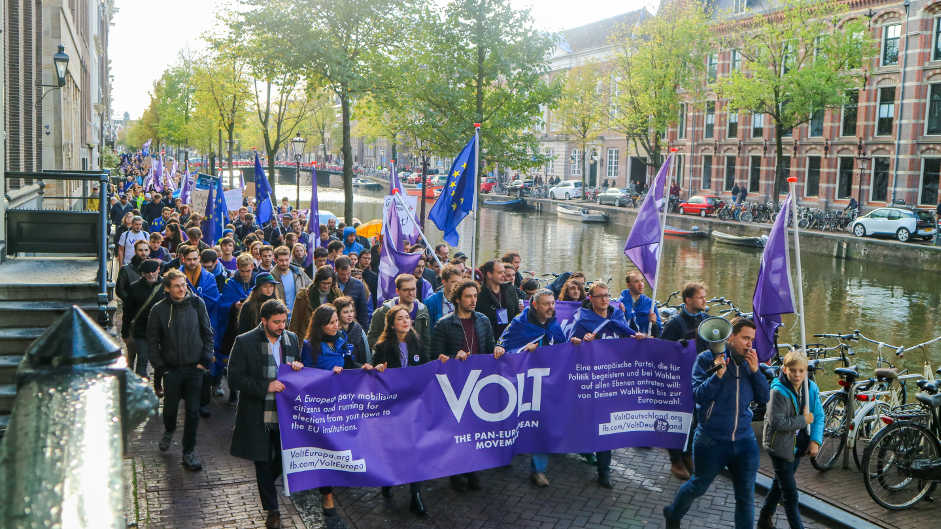 Eine lange Schlange von Menschen läuft mit Europa- und Volt-Flaggen über eine Straße neben einem Fluss. Vorne tragen die Leute einen großen Banner mit großem Volt-Logo.