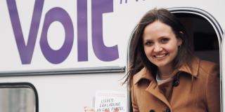 Carina Beckmann vor dem Volt-Wohnwagen und in der Hand das Buch, Eine Liebeserklärung an eine Partei, die es nicht gibt