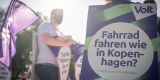 """Man sieht zwei Volter*innen wie sie in der Sonne Plakate und Fahne tragen. Auf einem Plakat steht """"Fahrrad fahren wie in Kopenhagen""""."""