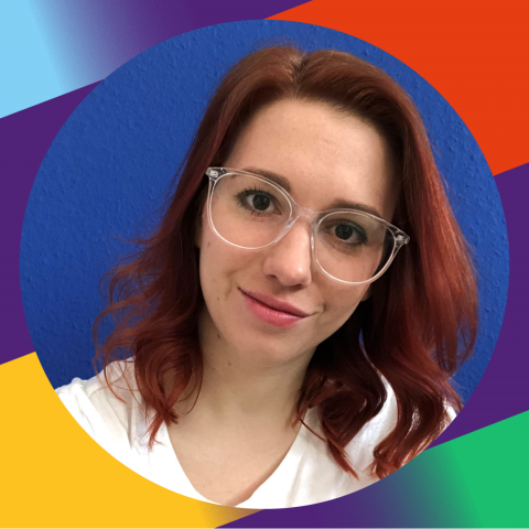 Ein Bild von Jennifer Scharpenberg vor einer dunkelblauen Wand. Sie hat rote, mittellange Haare, die leicht gewellt gestylt sind und trägt eine große Brille mit einem transparenten Rahmen. Sie lächelt mit schiefgelegtem Kopf in die Kamera und trägt ein weißes T-Shirt mit dem von Sternen umrandeten Volt-Logo.