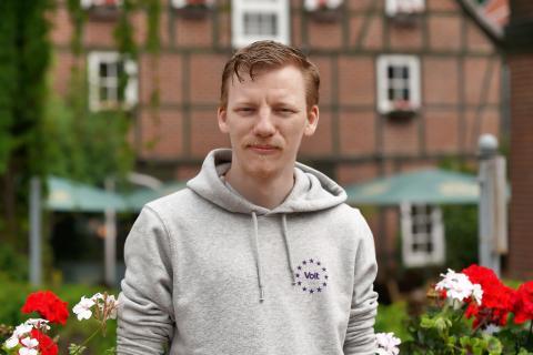 Michael Tamke vor einer Blumenhecke. Im Hintergrund ein Fachwerkhaus