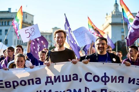 Mehrere Volter*innen bei einer Demonstation in Sofia, Bulgarien. Sie schwenken Volt-Fahnen und -Banner. In der Mitte ist Damian Boeselager zu sehen.