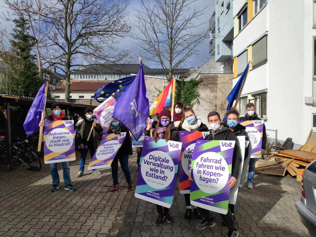Ein paar Menschen mit Volt-Flaggen, EU-Flaggen und Volt-Plakaten